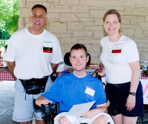 A young man seated in a wheel chair with a man and woman standing beside him. All are smiling.