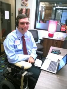Man seated in a wheel chair wearing a headset and preparing to show speech recognition software. He is preparing to demonstrate the impacts of digital accessibility.