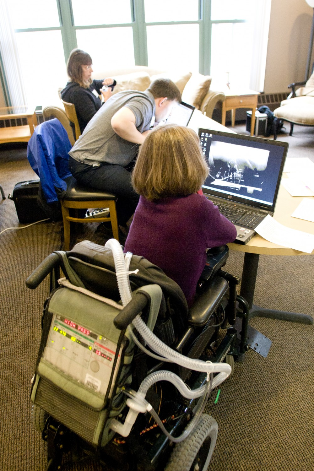 Woman in a wheel chair with a respirator working at a lap top.