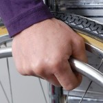 Photo of a male individual with his hand on the wheel of the wheelchair to move forward.