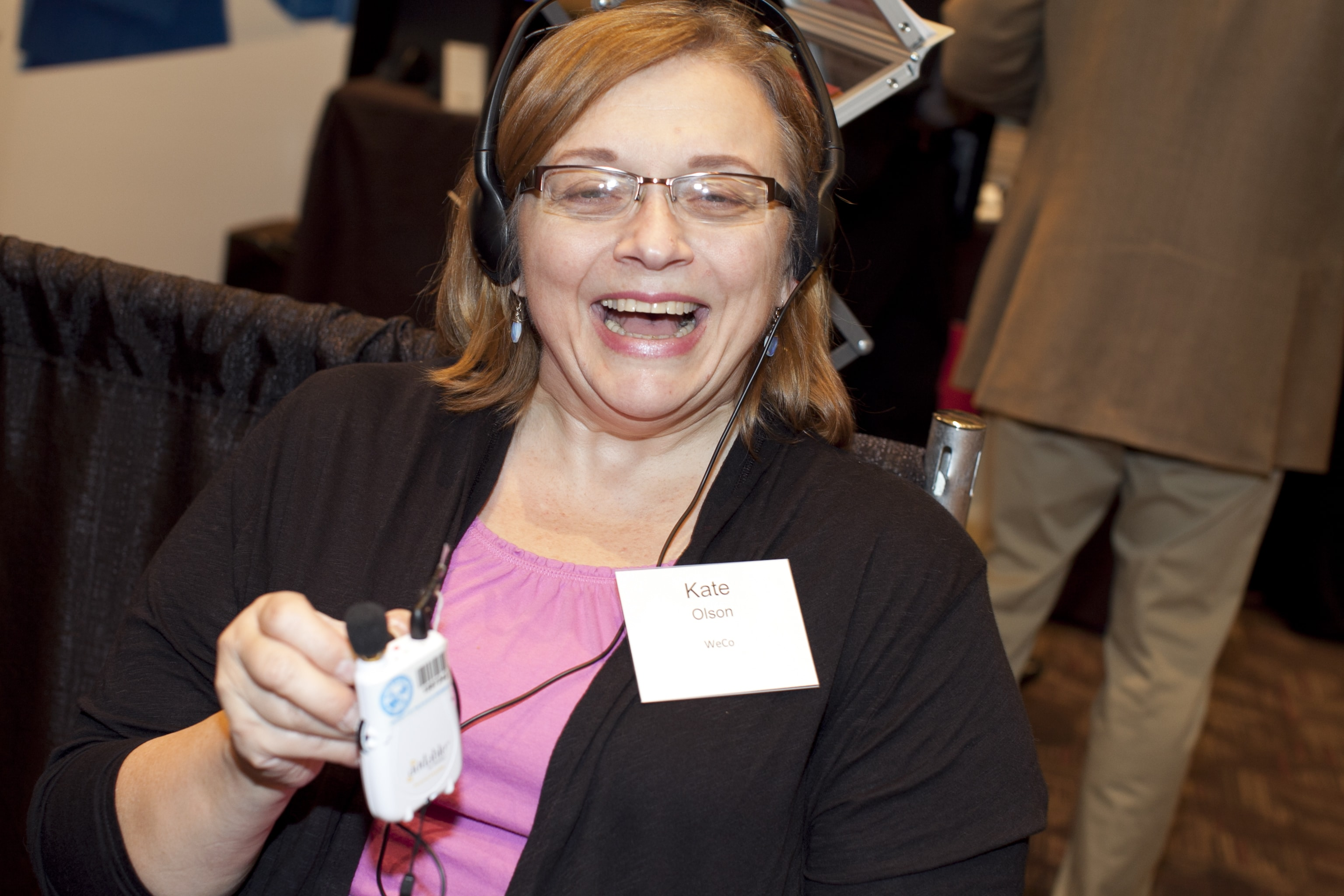 A WeCo Usability and Accessibility Tester holding a hearing amplification device.