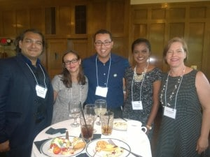 A group of 4 visiting leaders stand around a table at the closing reception with WeCo President, Lynn Wehrman.