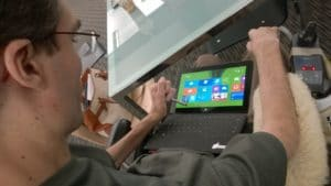 A WeCo Accessibility Specialist who works on digital accessibility services using a Microsoft Surface tablet.