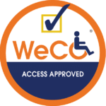 """WeCo Access Approved Seal: the word """"WeCo"""" with a person seated in the letter """"o"""" as if it's a wheel chair.  A check mark is over the logo and the words, """"Access Approved"""" are beneath it.  The logo is contained inside of an orange circle."""