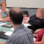 WeCo staff team members, who are living with a disability, seated around a conference table.
