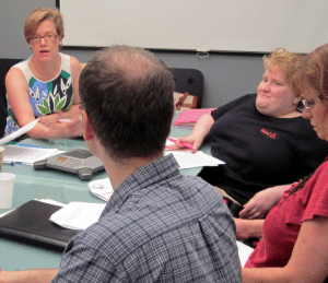 Lynn Wehrman seated around a conference table with WeCo staff team members.