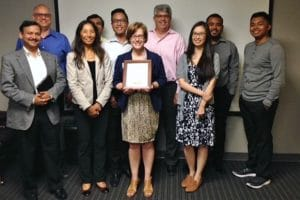 Group of smiling individuals standing together in a conference room after UX testing. WeCo President, Lynn Wehrman, is holding a certificate and standing at the center.