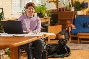 Women seated in a wheel chair at a desk in her home office. A service dog is on the floor next to her. All CTCs are living with a disability.