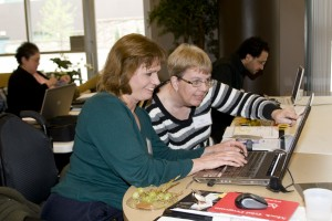 Two women seated in front of a lap top discussing information on the screen.
