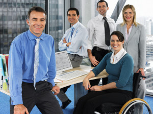 A group of office workers, including a woman seated in a wheel chair, seated around a desk and smiling.