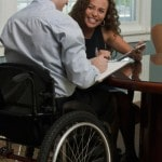 Businessman with spinal cord injury and a visually impaired Hispanic businesswoman discussing in an office