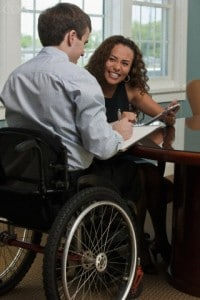 Businessman with spinal cord injury and a visually impaired businesswoman having a discussion in a conference room. Disability awareness is key for business function into the future.