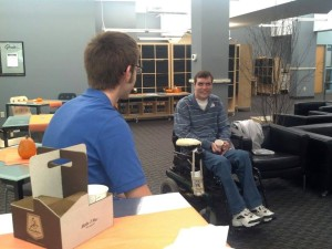 Two WeCo staff members having a discussion, Billy is seated on a stool and Chad is in a wheel chair.
