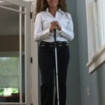 Visually impaired businesswoman standing with a cane in an office