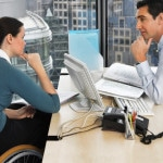 two office workers in meeting over a computer, one is in a wheelchair\