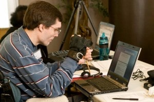 WeCo Accessibility Specialist, Chad Koch, using his wrist guard and pointer stick on his lap top computer keyboard.