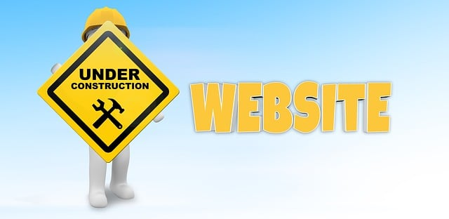 """A stick man with a construction helmet holding an """"under construction"""" sign with the word """"website"""" next to him."""