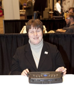 WeCo Certified Test Consultant, using a Braille Display, and smiling.