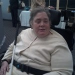 Photo of WeCo Lead CTC, Maureen Pranghofer.  Maureen is in a wheel chair holding a white cane.