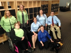 Group photo of WeCo's internal staff team of seven individuals. Two people in wheel chairs, one with a service dog.
