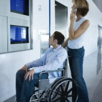 Man seated in wheelchair viewing flight arrive/departure board.