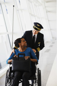 Woman seated in a wheelchair being assisted by an airline pilot.