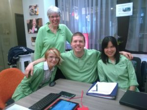 Four members of WeCo's staff team posing for a group photo. All are wearing matching green shirts.