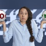 "Woman with a puzzled look on her face holding a ball that says ""no"" in her right hand and a ball that says ""yes"" in her left hand. A background of question marks is behind her."