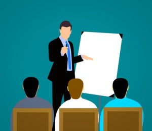 Illustration of a man standing in front of a class, pointing to a flip chart.
