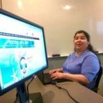 A WeCo Accessibility Specialist seated at a desk, smiling, with a computer monitor in the forground.