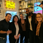 WeCo staff members posting with two Hamilton actors in a coffee house.