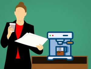 Woman holding a stack of papers and a coffee cup standing next to an espresso machine in an office.