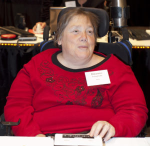 Maureen P, WeCo Sr. Client Relations' Specialist, sitting using a braille machine.