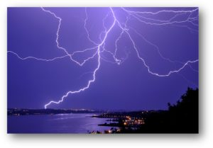 Photo of lightning strikes in a purple sky.