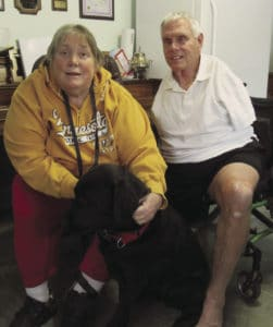 Maureen and Paul Pranghofer pose with Maureen's service dog, Walter.