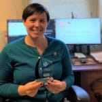 Kelli Ryan, WeCo Director of Operations, holding the company's 2020 Leading Disability Employer award trophy.