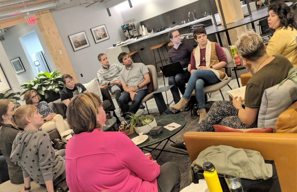 Accessibility Twin Cities MeetUp group assembled on sofas and chairs, having a discussion at WeCo's Minneapolis office.
