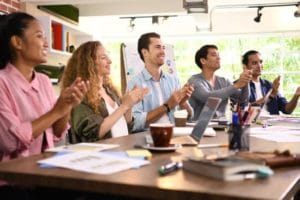 Group of business professionals seated at a conference table, applauding.