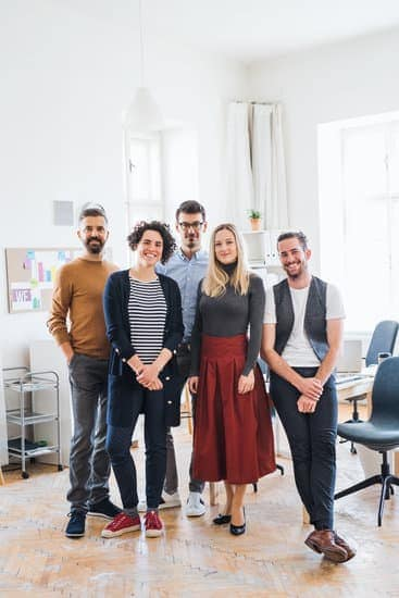 A full length portrait of group of young businesspeople standing in a modern office, looking at camera.