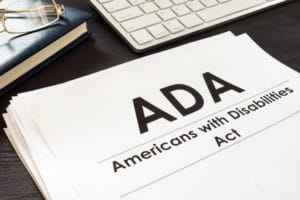 ADA-Americans with Disabilities Act - Paperwork next to a computer keyboard and a book with a pair of glasses on top of it.