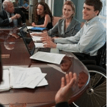 A man in a wheel chair and four co-workers attend an office meeting.